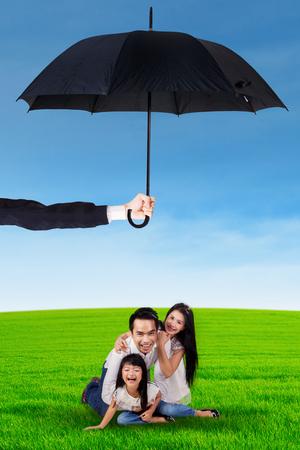 convivencia familiar: Retrato de familia feliz jugando juntos en el prado y protegido por el paraguas
