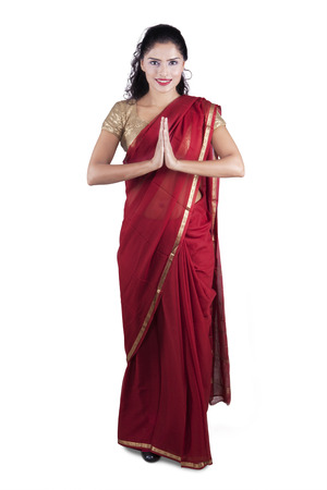 Full length of indian young woman wearing traditional clothes with greeting gesture, isolated on white background