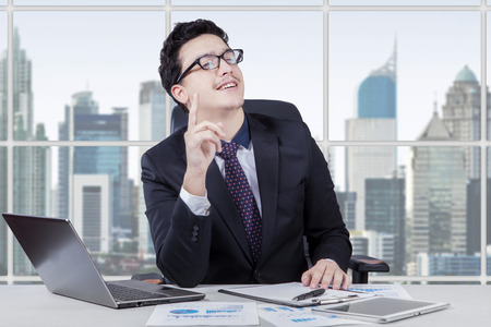 Picture of male entrepreneur wearing formal suit in the office and looks get bright idea with laptop and document on desk
