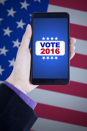 screen shot: Image of hand holding mobile phone with vote button on the screen, shot with american flag background