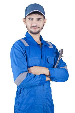 Picture of a young male mechanic standing in the studio while wearing uniform and holding a wrench, isolated on white background