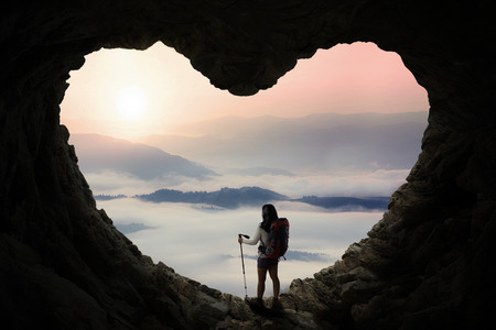 Silhouette of female hiker standing inside cave shaped heart symbol while holding stick pole and enjoy mountain view