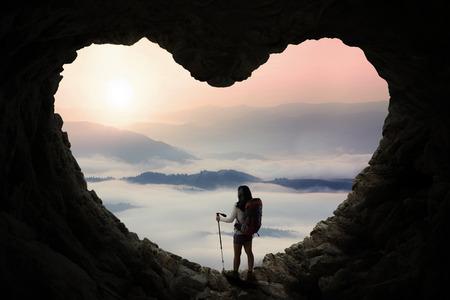uvnitř: Silueta ženské stopař stojící uvnitř jeskyně ve tvaru srdce symbol, zatímco drží hůl tyč a užít si výhled na hory