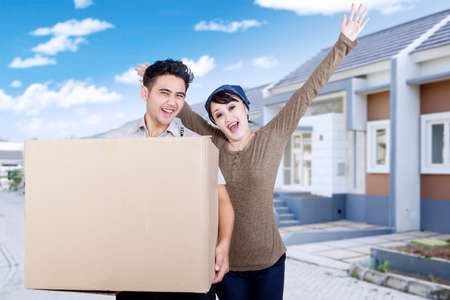 buy: Portrait of happy young couple carrying cardboard box in front of new house