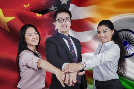 joining hands: Three young businesspeople joining hands in front of three national flag of chinese, american, and indian