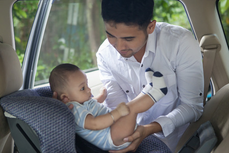Portrait of a father lifting his newborn baby from the car seat