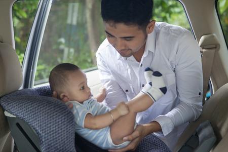 Portret van een vader opheffing van zijn pasgeboren baby uit het autozitje Stockfoto