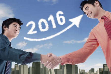 chinese businessman: Portrait of young chinese businessman shaking hands with his partner under cloud shaped number 2016