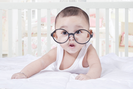 Portrait of sweet baby looking at the camera while lying on bedroom and wearing glasses