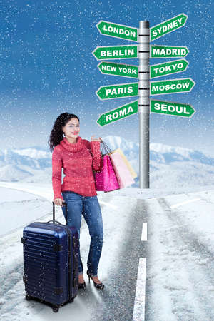 destinations: Image of happy woman standing on the road while holding suitcase and shopping bags with road sign of destination city for winter holiday