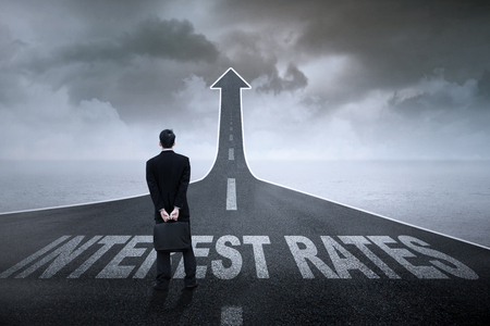 interest rates: Concept of growing interest rates. Entrepreneur standing on the highway with Interest Rates text on it