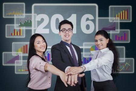 jovenes empresarios: Imagen de tres empresarios j�venes que muestran la unidad uniendo las manos juntas delante del gr�fico financiero con el n�mero 2016 Foto de archivo