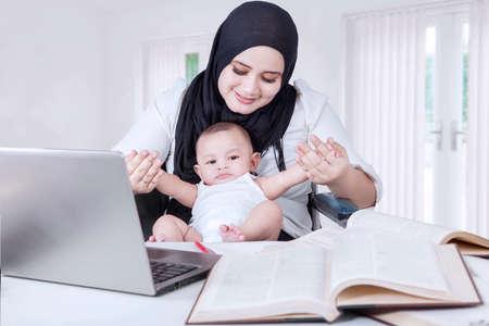 madre trabajadora: Foto de la joven empresaria asiática jugando con su bebé mientras trabaja en casa