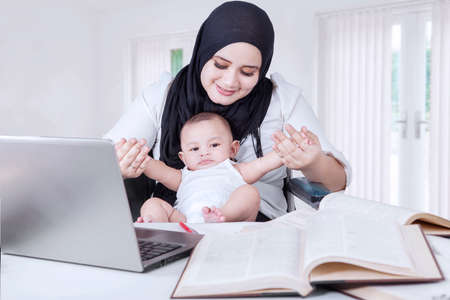 mom baby: Photo of young asian businesswoman playing with her baby boy while working at home