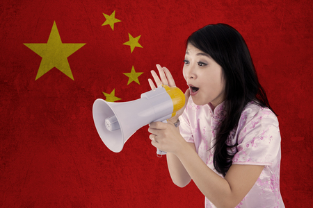 congratulate: Portrait of cheerful woman wearing cheongsam dress and congratulate Chinese new year with megaphone in front of Chinese flag
