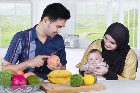home cooking: Portrait of happy asian family with their baby cooking together in the kitchen