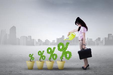 Afbeelding van een succesvolle jonge vrouw met een plant op de potten gevormde percentage symbool Stockfoto