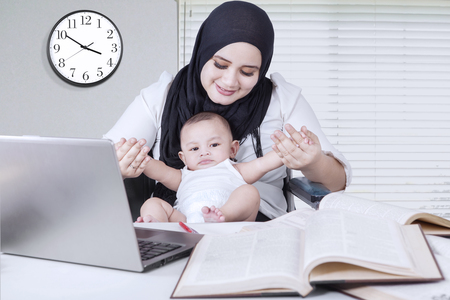 pretty baby: Pretty businesswoman playing with her baby boy while working at home Stock Photo