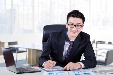 hombre escribiendo: empresario de Oriente Medio sonriendo a la cámara mientras se analiza el documento financiero con el ordenador portátil en el escritorio, un disparo en el sitio de la oficina Foto de archivo