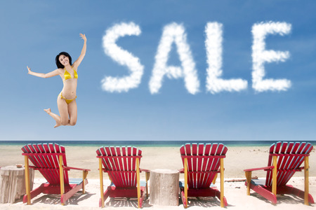whitehaven: Summer sale concept with girl jumping over beach chairs