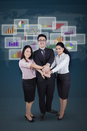 happy business team: Group of three multi ethnic businesspeople joining hands in front of financial graph