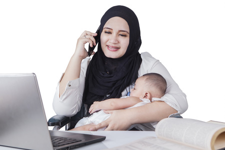 muslim baby: Portrait of happy muslim mother working with laptop while talking on the phone and nursing her baby