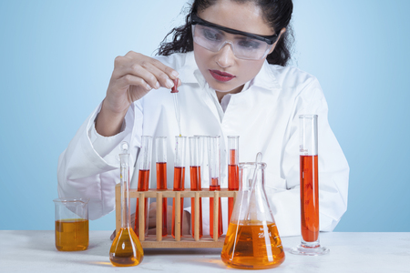 scientific research: Portrait of beautiful indian scientist doing research with test tube while wearing coat and glasses Stock Photo