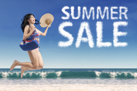 beach holiday: Attractive young woman enjoy freedom and jumping at seashore with summer sale cloud