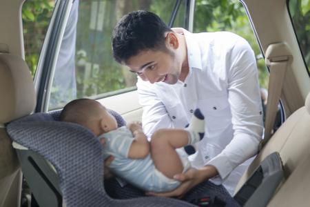 Retrato de joven padre poniendo su bebé recién nacido en el asiento del coche