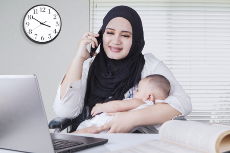 Portrait of muslim woman nursing her baby while working with laptop and talking on cell phone Stock Photo
