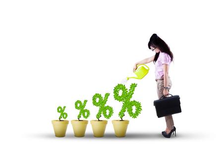 incremento: Empresaria joven que da el agua en el cultivo de plantas en forma de símbolo de porcentaje, aislado en fondo blanco