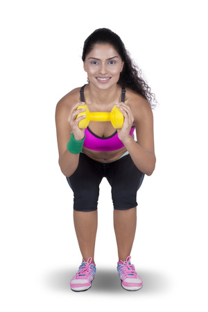 woman pose: Picture of young woman doing exercise while lifting dumbbell and squatting in the studio, isolated on white background Stock Photo