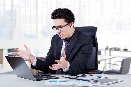 decepcionado: Retrato de joven empresario mirando a la pantalla del ordenador portátil en la oficina y se ve decepcionado, un disparo en el lugar de trabajo