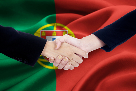 people shaking hands: Photo of agreement handshake with two worker hands, shaking hands in front of a Portugal flag background