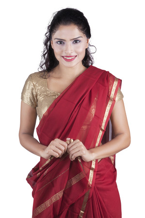 traditional costume: Beautiful indian young woman standing in the studio while wearing traditional dress, isolated on white background Stock Photo