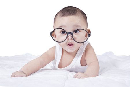 young boy smiling: Portrait of cute baby boy lying on the bed while wearing glasses and looking at the camera