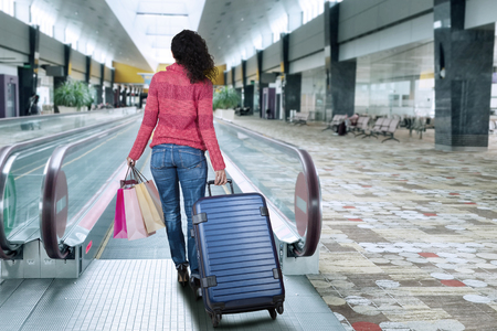 Attractive woman with winter clothes, walking to escalator at airport hall while holding suitcase and shopping bags