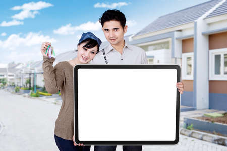 home loan: Picture of happy young couple smiling at the camera while showing keys of new house and empty billboard Stock Photo