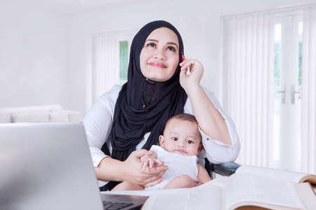mujer hijos: Retrato de mujer joven que lleva al bebé durante el trabajo y en casa soñando