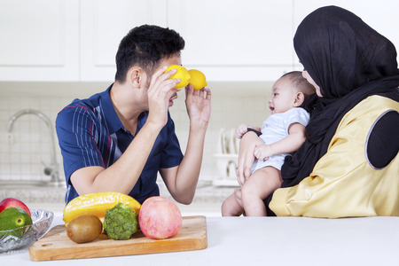 family life: Young father puts two oranges on his eyes and playing with his baby and wife in the kitchen