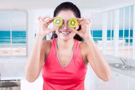 frutas divertidas: Mujer atractiva modelo cerrando los ojos con dos rebanadas de fruta de kiwi fresco en la cocina