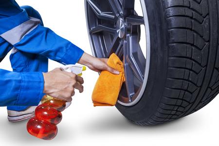 manos limpias: Imagen de manos de mecánico utilizando un paño y aerosol para limpiar la llanta representa aislado en el fondo blanco