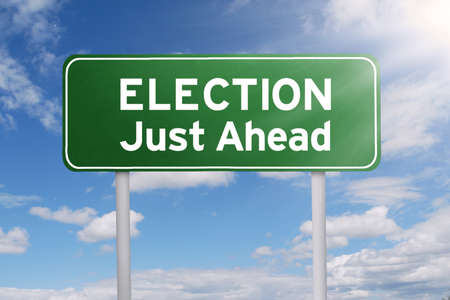 just ahead: Image of a road sign with a text of election just ahead under clear sky