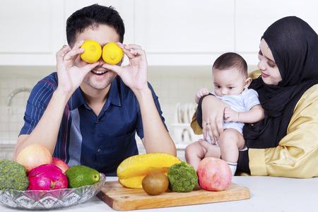 convivencia familiar: Dos padres felices y su pequeño hijo con fruta fresca y verdura en el vector. Un disparo en la cocina de su casa