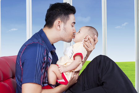 family sofa: Young man holds and kiss his baby while sitting on sofa near the window at home Stock Photo