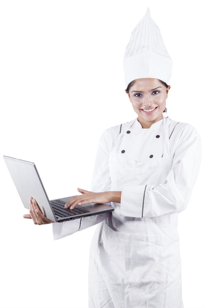 chef kitchen: Potrait of female cook in white uniform and hat using laptop computer, isolated on white background