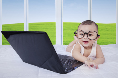 0 6 months: Attractive baby boy lying on bed with laptop computer and glasses, looking at the camera while laughing Stock Photo