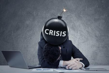 entrepreneur frustré de dormir sur la table avec une bombe de la crise financière sur la tête. Concept de la faillite et de la crise financière