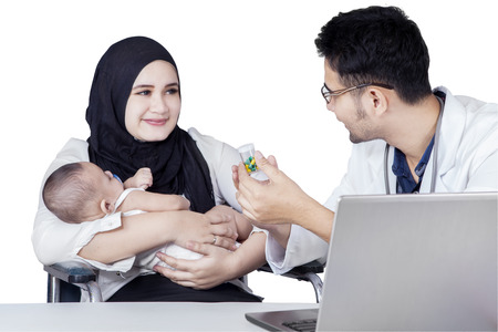 Muslim: Young mother and her baby boy listen a doctor explaining drugs in the bottle, isolated on white background Stock Photo