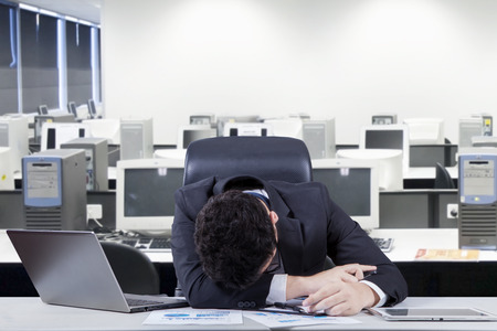 frustrated: Stressful male entrepreneur wearing formal suit and sleeping on the table with laptop and documents, shot in the office room